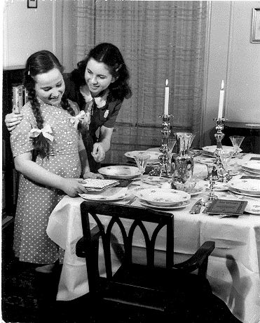 Two sisters set the Table for Passover Seder. New York, 1950's. Photo: Herbert Sonnenfeld. The Bernard H. and Miriam Oster Visual Documentation Center, the Sonnenfeld Collection